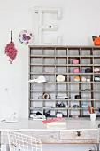 Balls of yarn and office utensils on wooden shelves above vintage desk