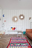 Round mirrors on white wooden wall, wooden bench and colourful rug in living area