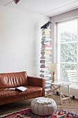 Leseecke mit Sitzpouf und Ledercouch neben Bücherständer und Tabletttisch mit Tischleuchte