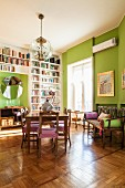 Floor to ceiling shelves and green walls in living room of period apartment