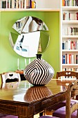 Black and white striped vase on wooden table in front of mirror