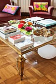 Books on glass-topped coffee table with gilt frame