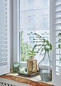 A rustic oak window sill decorated with vases and tea lights with a romantic lace curtain in the window