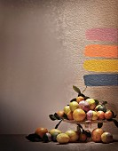 Citrus fruits on cake stand and paint samples on wall; photographic art