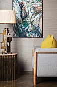 Grey armchair and table lamp below painting on wall