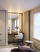 Illuminated dressing table with mirror in niche between fitted wardrobe and window with floor-length curtains in bedroom