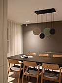 Exotic-wood table and upholstered armchairs below designer pendant lamps with disc-shaped lampshades