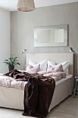 Double bed with loose-covered frame below mirror on grey wall