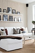 White sofa, accessories in earthy tones and pictures on narrow shelves on beige wall