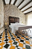 Double bed with antique headboard against traditional stone wall on multicoloured geometric tiled floor