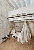 Restored bedroom with stone wall, white wooden gallery and patterned tiled floor