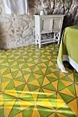 Zweifarbiger Fliesenboden mit geometrischem Muster in Schlafzimmer mit Natursteinwand und Vintage Schränkchen