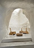 Wicker rocking chairs and low coffee table in unusual, white, cave-like lounge area