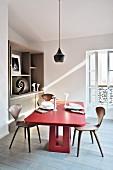 Roter Eichentisch und Designerstühle unter Pendelleuchte im Esszimmer