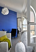 Large white paper lanterns in between arched window and sofa in living area with blue partition wall