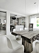 Weathered wooden table and white classic Panton chairs in front of open-plan kitchen