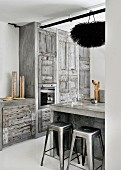 Concrete kitchen country and classic bar stools in front of rustic grey fitted kitchen