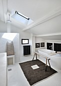 Skylight, shower area and free-standing white bathtub in attic bathroom