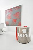 Baumstamm-Kunstobjekt mit roten Steinen vor moderner Kunst an weißer Wand