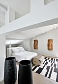 Objets d'art made from bark, black vases and black and white rug in white bedroom