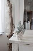 Kleiner Tannenbaum mit Kunstschnee und mit Stoff umwickelt