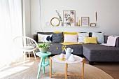 Hocker und Tablettisch vor grauem Sofa mit pastellfarbenen Kissen