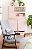 Patterned cushion on retro armchair in front of pink kitchen dresser