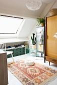 Raum mit Schräge, Dachfenster und Retromöbeln