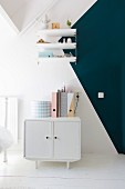 Small white retro cabinet below shelves mounted on two-tone wall