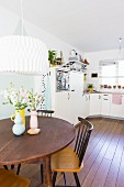 Retro vases on round dining table and view into open-plan kitchen