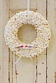 Hand-made popcorn wreath with bird ornaments and ribbon hung on door