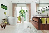Free-standing white bathtub, potted palm, green accents and modrn washstand in elegant bathroom