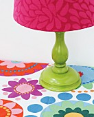 Green-painted table lamp base with pink-patterned lampshade on tablecloth with retro pattern of colourful flowers