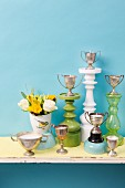 DIY candles poured into silver trophies and decoratively arranges against pale blue wall