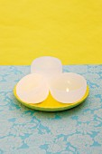 DIY bowl-shaped candles on yellow plate against yellow background