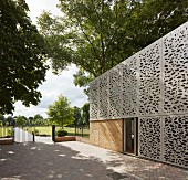 Building with modern perforated façade elements, paved courtyard and view into park-style gardens