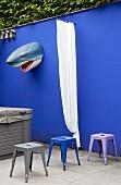 Blaue Gartenmauer mit Haikopf, Vorhang und bunten Metallhockern