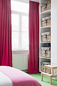Red curtains and storage baskets on white shelves in bedroom