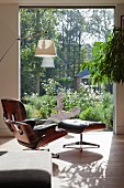 View past designer armchair through window and into garden
