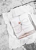 Romantisch verschnürte DIY gefärbte Stoffbündel auf weißem Seidenpapier