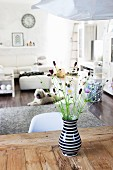 Black and white vase of wild flowers on rustic wooden table