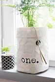 Green asparagus in white paper bag with printed lettering on windowsill
