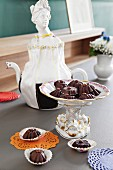 An elegant porcelain serving dish with home-made chocolate pralines in front of a nostalgic porcelain jug