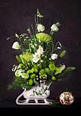 Weihnachtliches Blumengesteck in schlittenförmiger Vase
