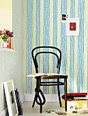 Grün-blaue Vliestapete mit Fischgrätmuster, davor Holzstuhl im Thonetstil mit Fotoalbum und Fotokiste am Boden