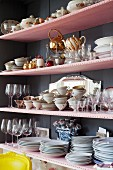 Crockery stacked on pink shelves