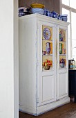 White vintage cupboard with painted panels and blue and white crockery on top
