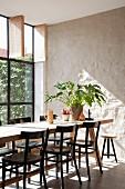 Esstisch mit schwarzen Stühlen vor verputzter Mauer und Fabrikfenster