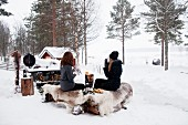 Two women sitting in snowy landscape next to fire having winter picnic