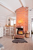 Wood-burning stove and brick chimney breast next to hatch leading to kitchen
